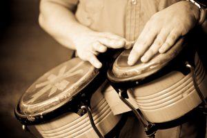 Hands playing bongo.